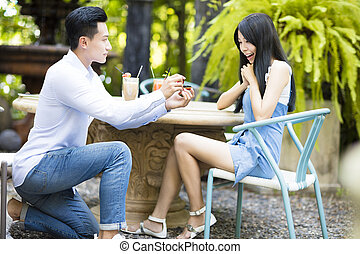 Man proposing to girlfriend offering engagement ring in...
