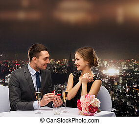 man proposing to his girlfriend at restaurant - restaurant,...