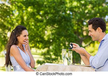 Man proposing woman at an outdoor café