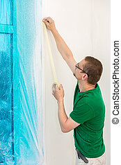 Man protecting window with foil before painting