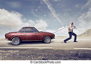 Man pulling car