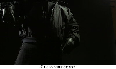 Man pulling out a gun from his jacket pocket in the darkness
