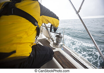 Man Pulling Rope By Winch On Sail Boat