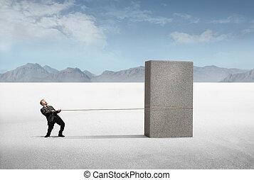 Man pulling stone - Businessman pulling heavy rock in winter...