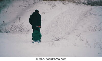 Man pulls a daughter sledding in the winter forest