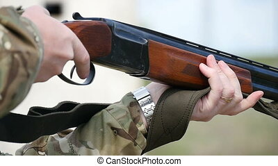 Man pulls a trigger and shoots from a one barrel shotgun in a field in slo-mo