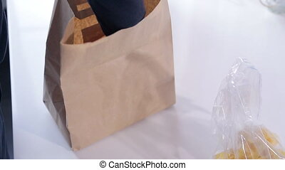 Man pulls out a paper package seafood vacuum packed and pasta.