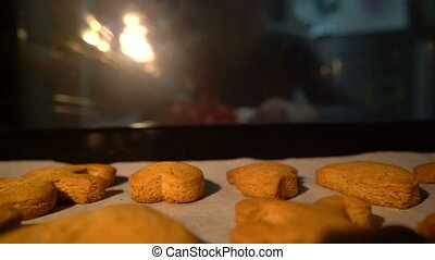 man pulls out ginger biscuits out of the oven, view from the...