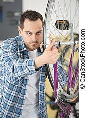 man pumping wheel bike