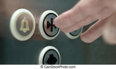 Man pushes a button opening elevator doors. Close up - A man...