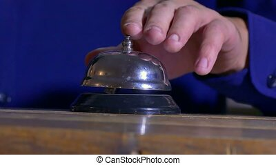 man pushes a call bell at the hotel arm - man pushes a call...