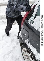 Man pushing car stuck in snow
