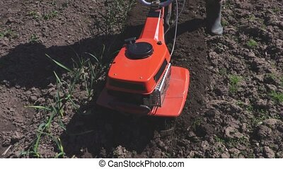 Man pushing cultivator