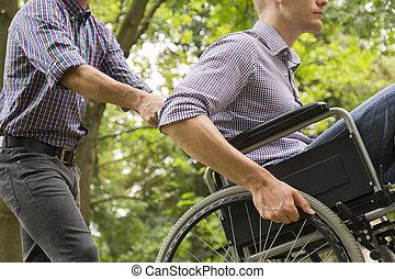 Man pushing his friend in wheelchair