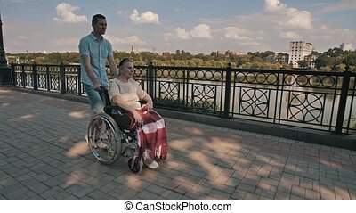 Man pushing old woman on a wheelchair