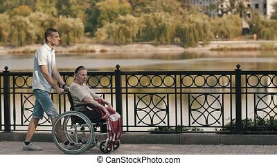 Man pushing senior woman on a wheelchair