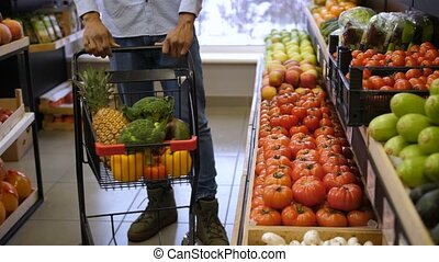 Man pushing shopping cart in grocery store - Midsection of...