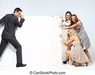 Man pushing through a board against women