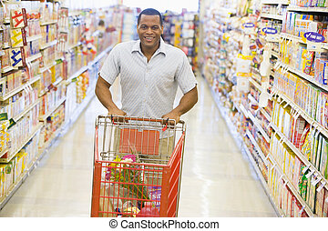 Man pushing trolley along supermarket aisle - Man pushing...