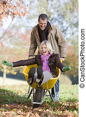 Man pushing wife in wheelbarrow