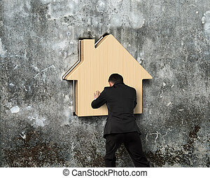 Man pushing wooden house into hole of concrete wall