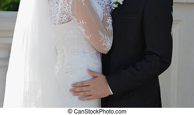 Man put hand on the bride's hip
