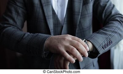 Young man in suit put on wrist watch. Groom dresses. Handsome male businessman is waiting for a meeting. Hand with a clock close up. Waits. Looks at the clock, time. Wristwatch on man arm. Slow motion