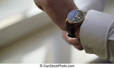 Man put on wrist watches near window