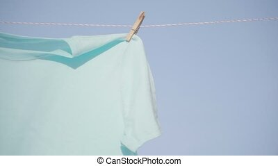 Man put pins clips on drying laundry t-shirt hanging...