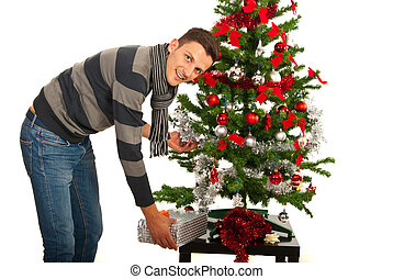 Man put present under tree