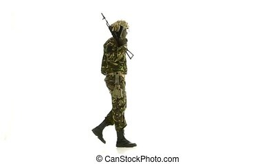 Man put the gun on his shoulder and looks around. White backgraund