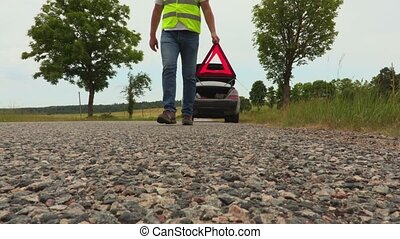 Man put warning triangle on the road near car