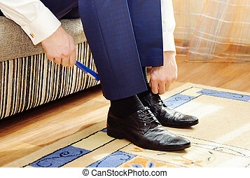 Man puting on his shoes.