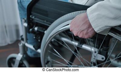 Handicapped man on a wheelchair alone in room
