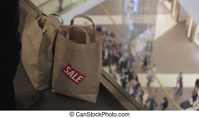 Man puts brown bags with sale sticker on it on floor in mall on black friday. Crowd on background