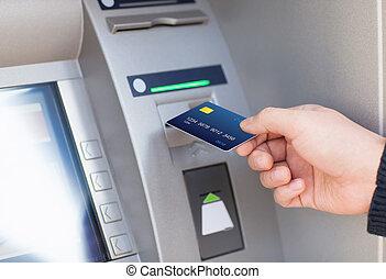 man puts credit card into ATM