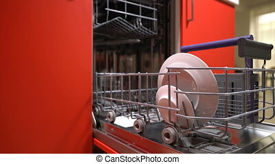man puts dishes in the dishwasher to wash them