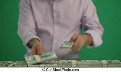 Man Puts Dolars in a Heap