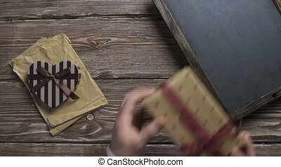 Man puts gift boxes one by one to wooden desktop - Top view,...