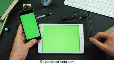 Man puts his glasses by the tablet with green screen on the table