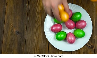 Hands put on a plate the Easter decorated and painted colored eggs during a Christian holiday Pascha or Resurrection Sunday