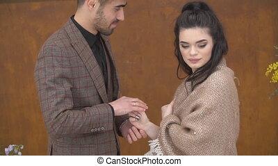 man puts on a wedding ring