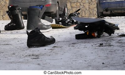 Man puts on shoes for snowboarding near the car on a...