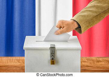 Man putting a ballot into a voting box - France