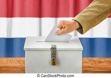 Man putting a ballot into a voting box - Netherlands