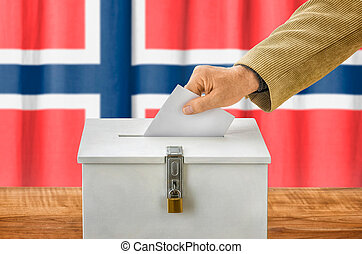 Man putting a ballot into a voting box - Norway