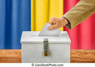 Man putting a ballot into a voting box - Romania