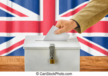 Man putting a ballot into a voting box - United Kingdom