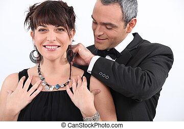 Man putting a necklace on his lover