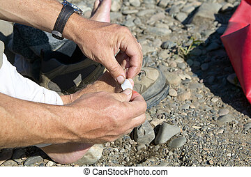 Man putting a sticking plaster on his toe